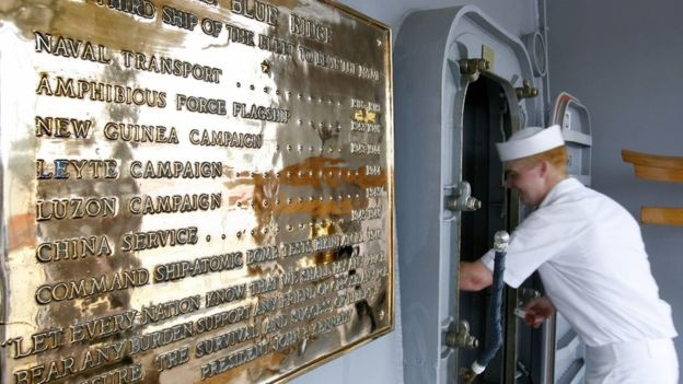 A US Navy sailor enters the deck of the USS Blue Ridge next to a plaque which lists the ship's involvement in several service campaigns, during a media tour on board the ship at Westport near Port Klang, 06 March 2006.