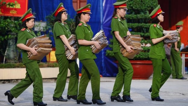 Policewomen carry case report files on the female prisoners to be freed at a local jail in the suburbs of Hanoi on August 31, 2015.
