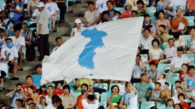 "South Korean supporters wave ""reunification"" flags for the North Korean football team during a match between South and North Korea at the East Asian Football Championship in Jeonju, Seoul, 4 August 2005"
