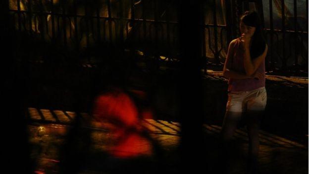 Một phụ nữ hoạt động mại dâm chờ khách trên phố Hà Nội