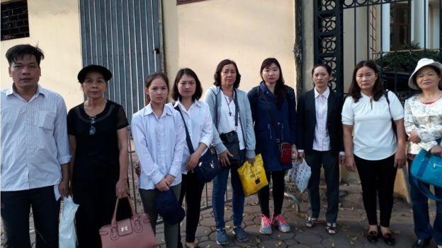 Thân nhân các nhà hoạt động đứng bên ngoài toà trong giờ toà nghỉ trưa