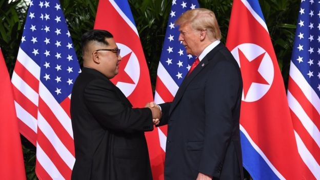 Mr Trump and Mr Kim shake hands