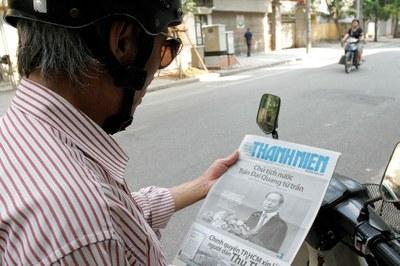 Một người dân trong nước đang xem bảng tin Chủ tịch nước Trần Đại Quang từ trần